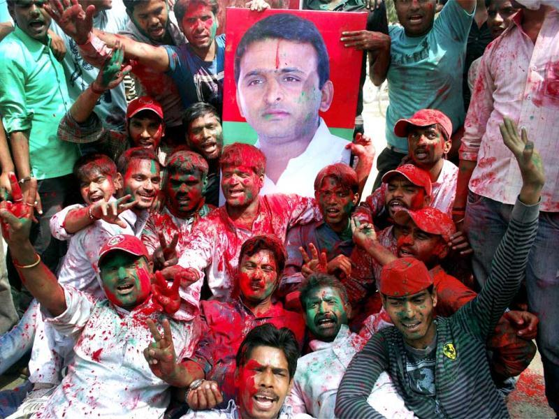 Samajwadi Party workers celebrate with a poster of Akhilesh Yadav in Allahabad. PTI