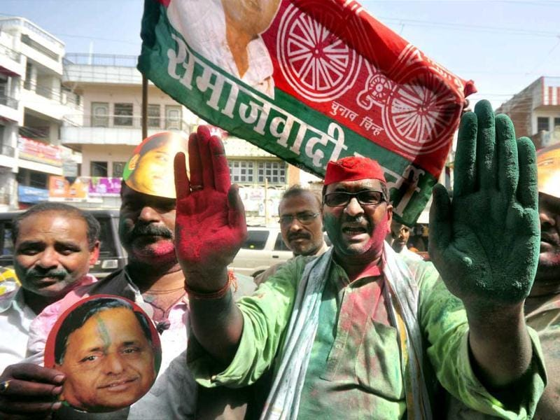 Samajwadi Party workers celebrate with their leader Mulayam Singh Yadav's cutout and party flag in Allahabad. PTI