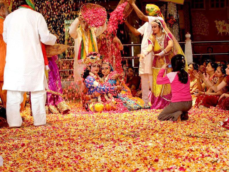 Artistes performing Radha Krishna dance with flowers to mark holi festival during the Fagun Utsav at historical Radha Govind Devji temple in Jaipur. Agencies