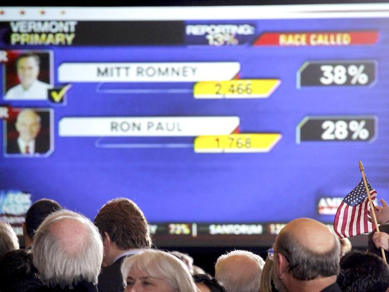A child holds a US flag as supporters of Republican US presidential candidate and former Massachusetts governor Mitt Romney view a screen showing Vermont primary results at his