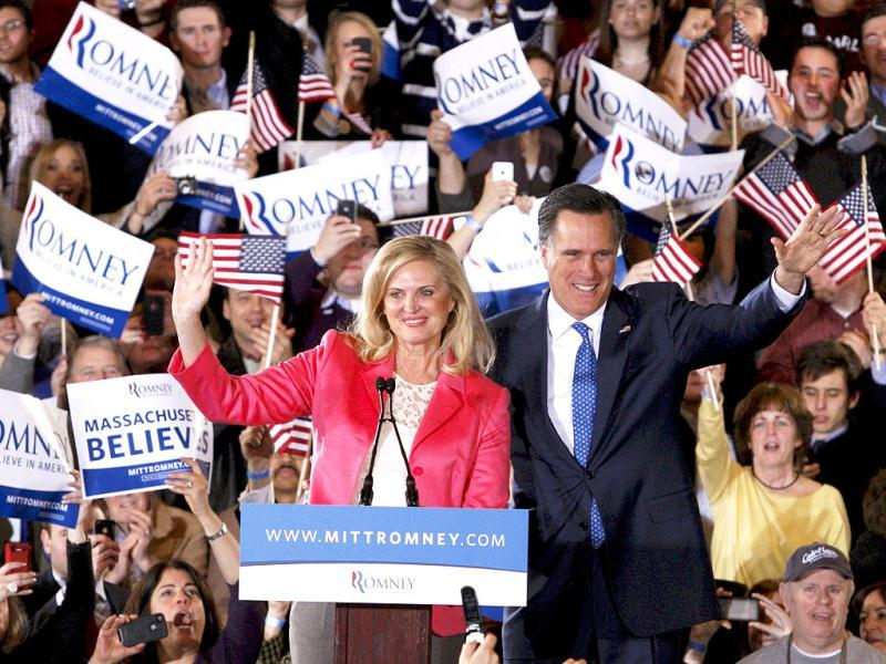 Republican US presidential candidate Mitt Romney (R) waves to supporters along with his wife Ann at his