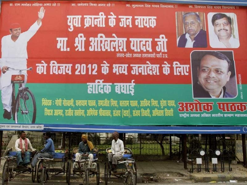 Rickshaw pullers rest in front of a hoarding of Samajwadi Party members in Lucknow. AP/Rajesh Kumar Singh