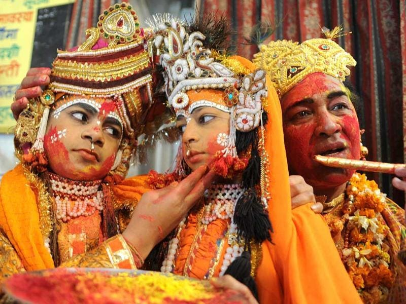 Devotees dressed as Lord Krishna and Radha (C) pose as they play with colours at a temple in Amritsar. AFP/Narinder Nanu