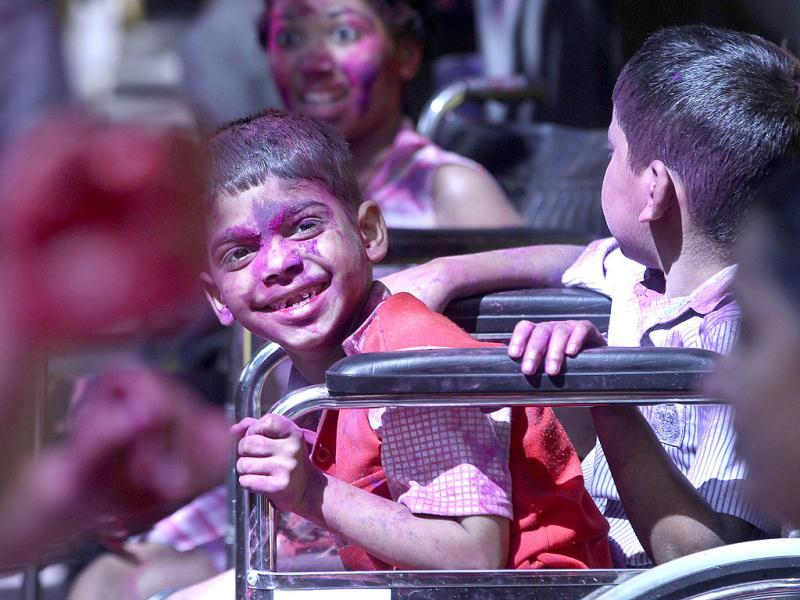 Physically challenged child smiles as he celebrates Holi, with friends at a school in Mumbai. AP Photo/Rajanish Kakade