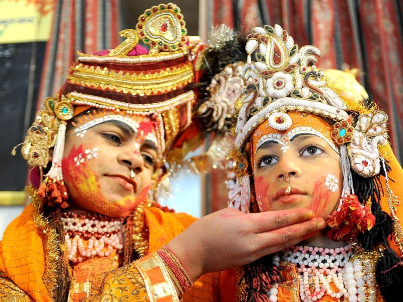 Devotees dressed as Lord Krishna and Radha pose as they play with colours at a temple in Amritsar. AFP Photo/Narinder Nanu