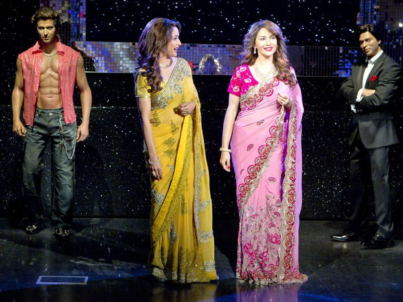 Madhuri admires her wax statue, while the replicas of Hrithik Roshan (L) and Shah Rukh Khan (R) look on.