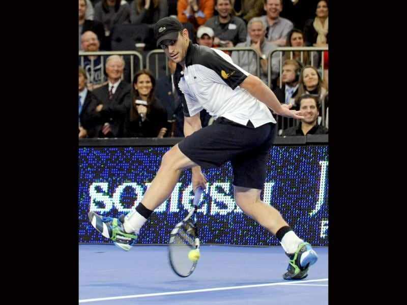Andy Roddick returns the ball with a shot between his legs to Roger Federer during the BNP Paribas Showdown exhibition tennis match, at Madison Square Garden in New York. (AP Photo/Bill Kostroun)