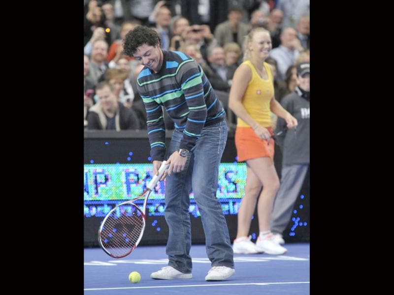 Golfer Rory Mcilroy, left, tees up a tennis ball to hit to Maria Sharapova as Caroline Wozniacki looks on in the BNP Paribas Showdown exhibition tennis match, at Madison Square Garden in New York. (AP Photo/Bill Kostroun)