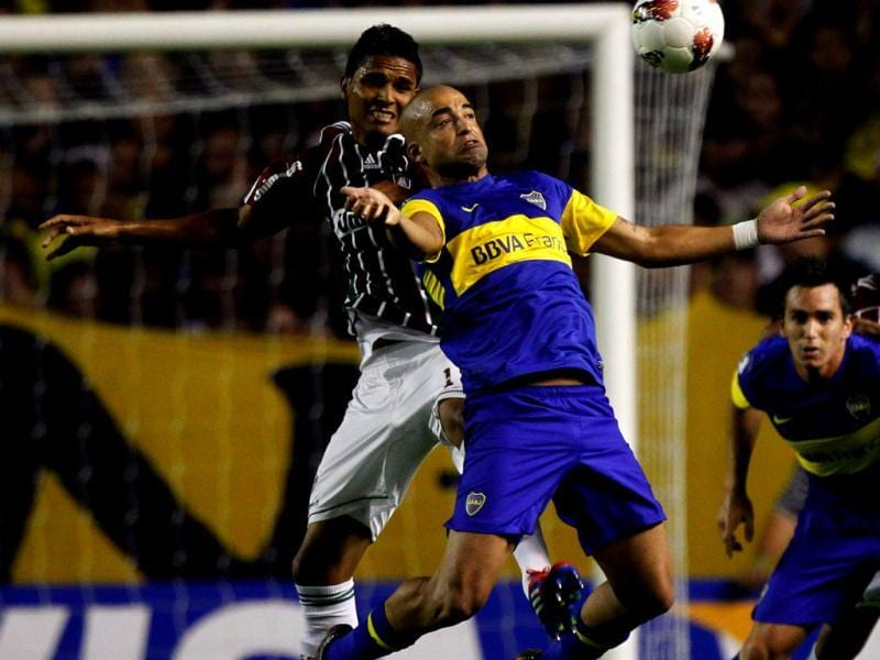 Santiago Silva (front) of Argentina's Boca Juniors hits the ball with his chest in front of Anderson of Brazil's Fluminense during their Copa Libertadores soccer match at La Bombonera stadium in Buenos Aires. Reuters/Enrique Marcarian