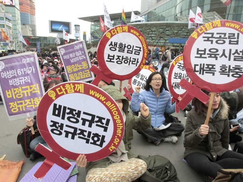 South Korean female workers shout slogans during a rally to mark International Women's Day in Seoul, South Korea. The letters read 'Preserve a living wage and hire more temporary employees'. AP/Ahn Young-joon