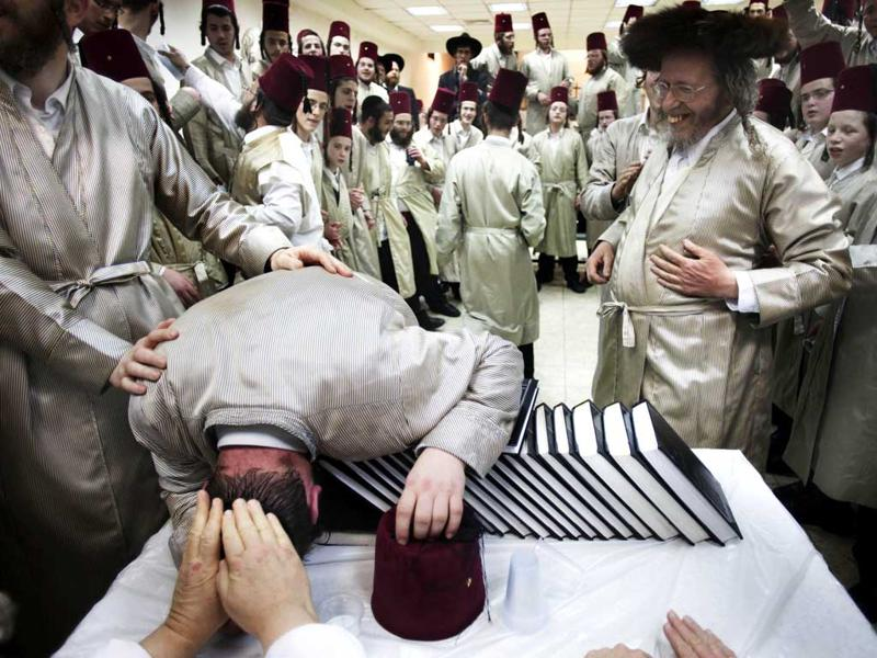 Utra-orthodox Jewish men celebrate Purim inside a synagogue in Jerusalem. The Jewish holiday of Purim celebrates the Jews' salvation from genocide in ancient Persia, as recounted in the Scroll of Esther. (AP Photo/Bernat Armangue)