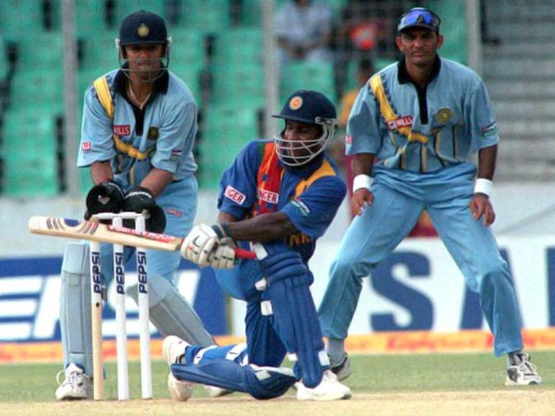 Wicketkeeper Rahul Dravid and former captain Mohammad Azharuddin (R) watch Sri Lankan skipper Sanath Jayasuriya (C) batting during his knock of 105 of 116 balls against India in the four-nation Asia Cup limited-overs tournament at the Bangabandhu national stadium in Dhaka on 01 June, 2000. AFP PHOTO/Mufty Munir