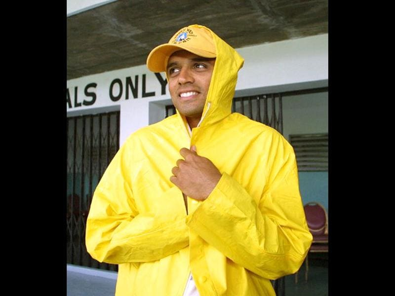 Rahul Dravid puts on a raincoat on 26 May 2002 at Sabina Park in Kingston, Jamaica after rain forced the cancellation of the second day of the international matches between India and the West Indies. AFP Photo/Timothy A Clary