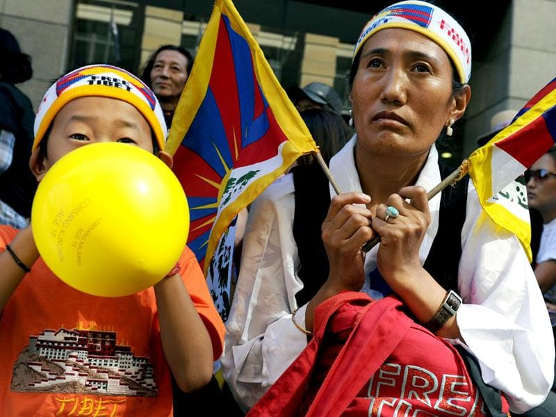 Jinpa Lhamo (R) listens to guest speakers during a rally marking the 53rd anniversary of the Tibetan uprising in Sydney. AFP/ Torsten Blackwood