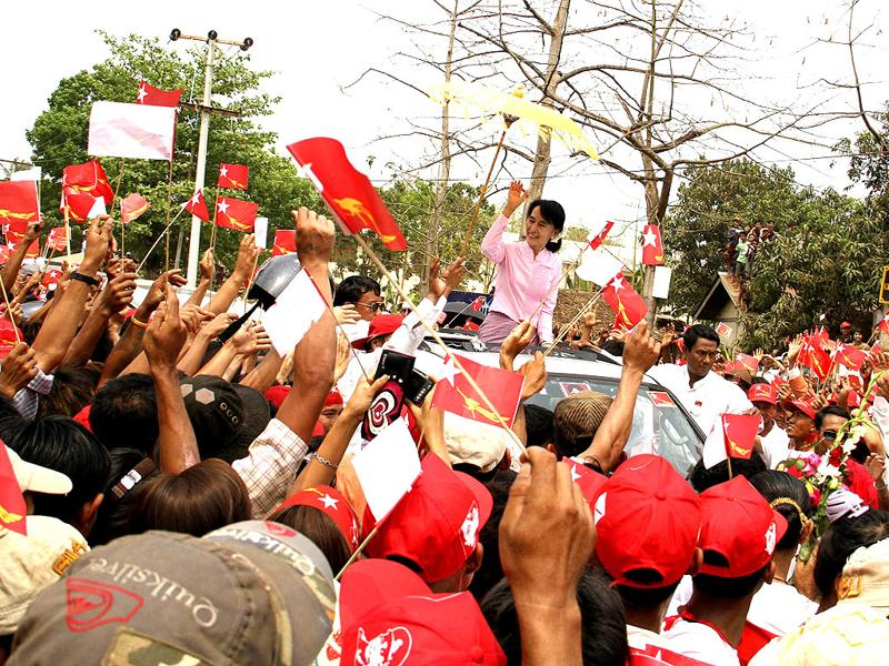 Myanmar pro-democracy leader Aung San Suu Kyi, center, waves to supporters from her vehicle as she arrives at Bee Lin township, Mon State, Myanmar, on her way to elections campaign to Mawlamyine. (AP Photo/Khin Maung Win)