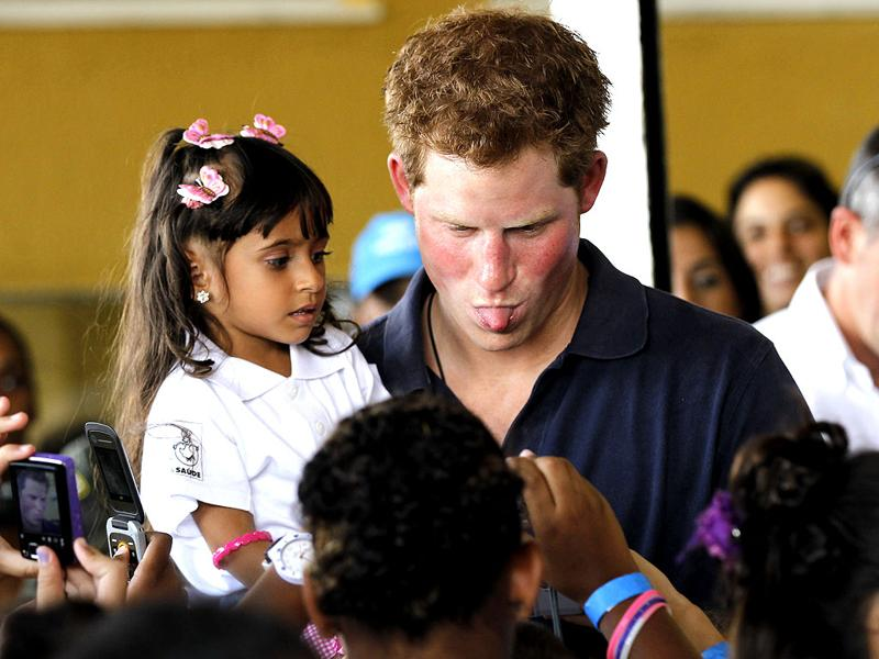 Prince Harry playfully sticks out his tongue as he poses for a photo during his visit to the Complexo do Alemao slum, in Rio de Janeiro, Brazil. (AP Photo/Silvia Izquierdo)