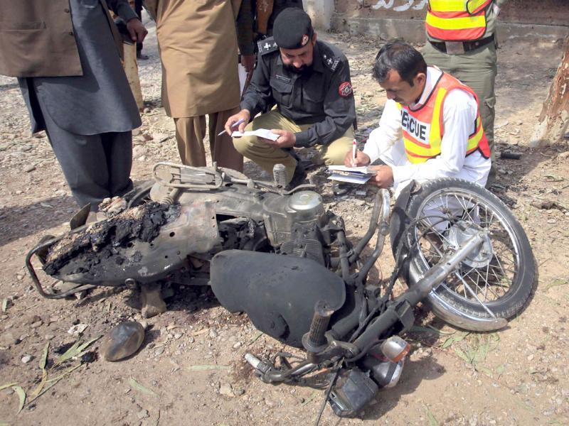 Police and rescue workers inspect a damaged motorbike at the site of a suspected suicide bomb attack in the outskirts of Peshawar. Reuters/Fayaz Aziz
