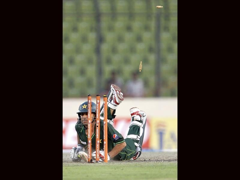 Bails fly in air as Pakistan's Saeed Ajmal dives to make it to the crease to avoid a run-out by Bangladesh's captain Mushfiqur Rahim during their Asia Cup cricket match in Dhaka, Bangladesh. AP/Aijaz Rahi