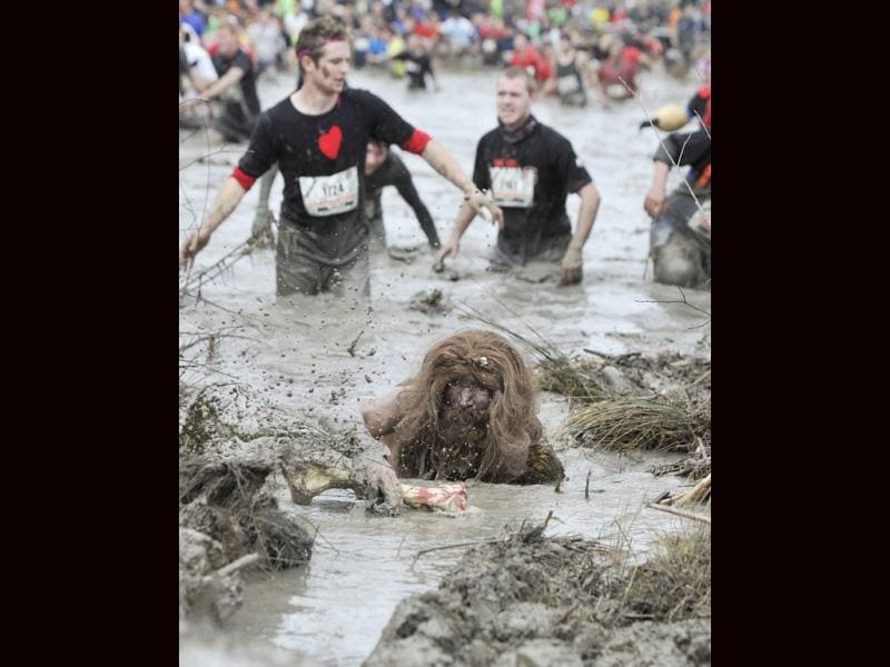 Competitors run through muddy water during the Strongman Run in Thun, Switzerland. AP Photo/Keystone/Peter Schneider