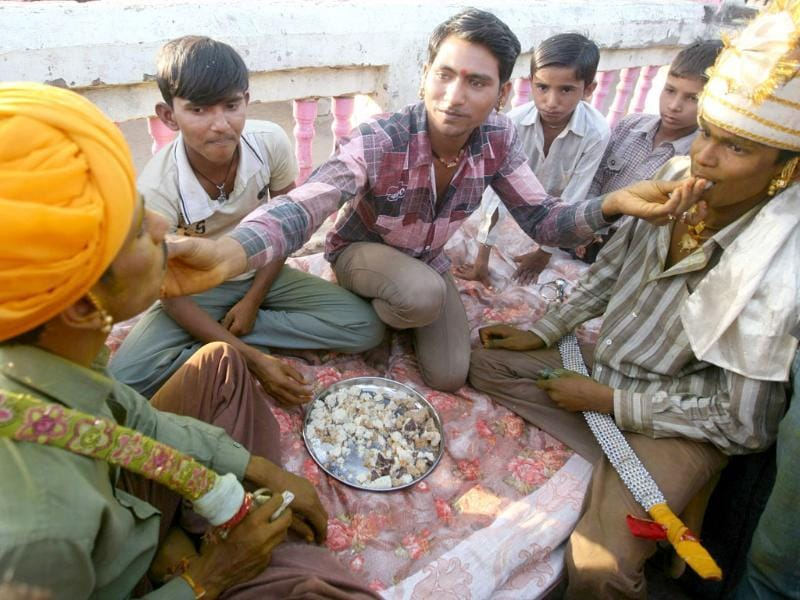 A man offers sweets to groomsmen from the Saraniya community during a ritual on the eve of their wedding at Vadia village in Gujarat. Reuters/Amit Dave