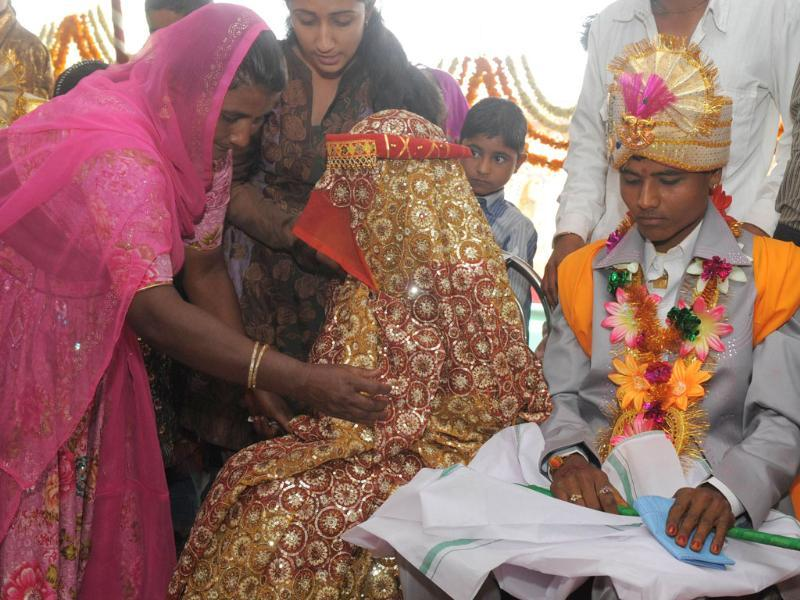 A relative (L) comforts a bride as she participates in a mass marriage in Vadia, a so-called 'village of prostitutes', in Gujarat. Eight young women whose mothers are sex workers were married under a plan to save them from being pushed into the world's oldest profession. AFP/Sam Panthaky