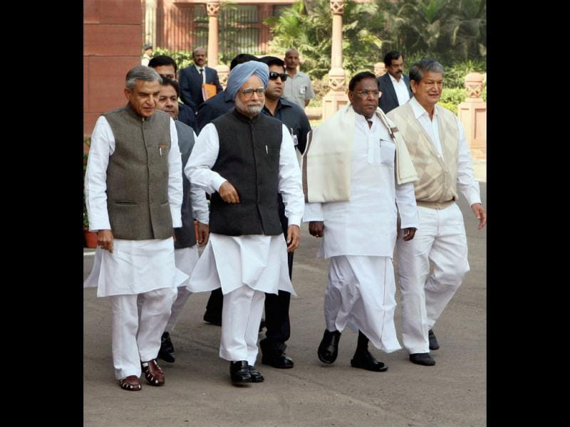 Prime Minister Manmohan Singh, flanked by parliamentary affairs minister Pawan Kumar Bansal and ministers of state V Narayanasamy (R) and Harish Rawat, arrives at Parliament House on the first day of the budget session, in New Delhi on Monday. Vijay Kumar Joshi