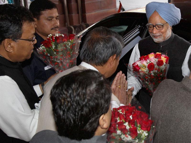Prime Minister Manmohan Singh being received by Harish Rawat, MoS for Parliamentary Affairs on the opening day of the Budget session in New Delhi. PTI Photo by Shahbaz Khan