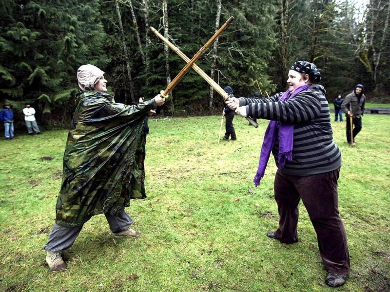 Two women learn how to sword fight at a