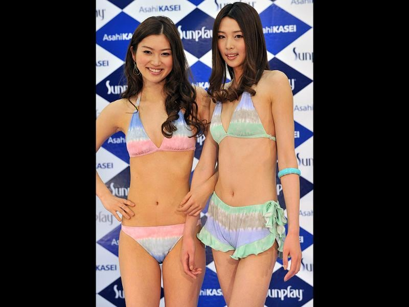 Japanese model Saemi Ikeda (L) and Chinese model Hu Nan display the latest swimsuit designs by Japanese textile maker Asahi Kasei during a campaign in Tokyo. AFP Photo/Yoshikazu Tsuno