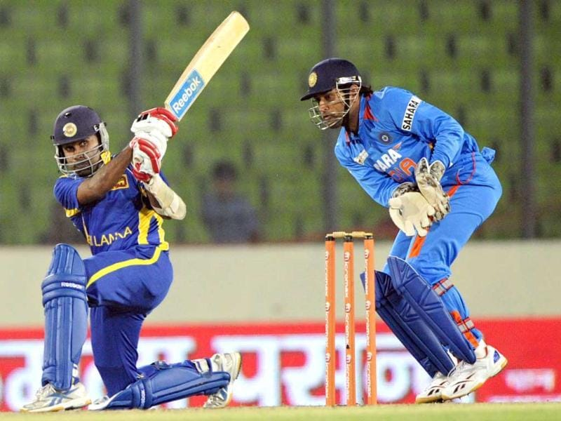 Sri Lankan captain Mahela Jayawardene (L) plays a shot as his Indian counterpart Mahendra Singh Dhoni looks on during the one day international Asia Cup cricket match at The Sher-e-Bangla National Cricket Stadium in Dhaka. AFP/Munir uz Zaman