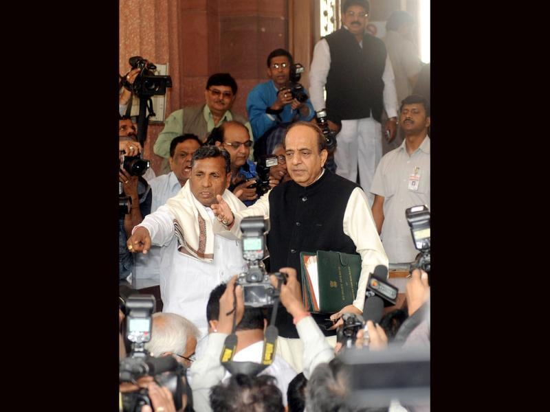 Dinesh Trivedi (C) gestures as he arrives at Parliament flanked by minister of state for railway Muniyappa ((L) as they are surrounded by media representatives in New Delhi.Indian Railways Minister Dinesh Trivedi presents the railway budget for the fiscal year to March 2012-13 in Parliament. AFP Photo/Raveendran