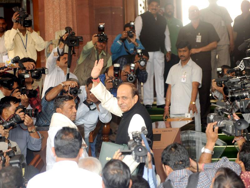 Dinesh Trivedi waves as he arrives at Parliament flanked by minister of state for railway Muniyappa ((L) as they are surrounded by media representatives in New Delhi. AFP Photo/Raveendran