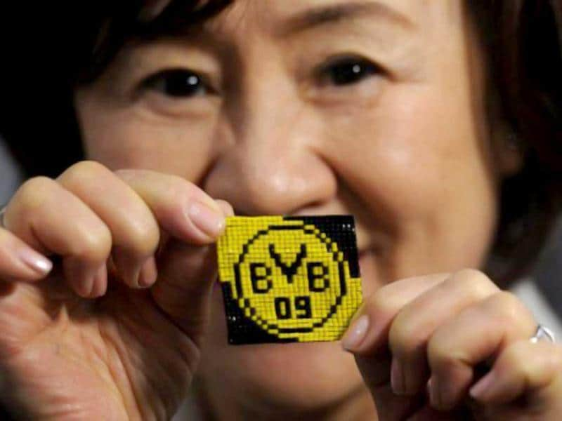 Japanese pearl weaver Takako Sako poses with a woven logo of German first football division club Borussia Dortmund at the 'Creativa' fair for creative design and leisure. AFP/Patrik Stollarz