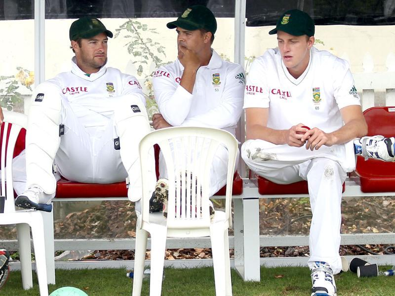 Mark Boucher (L), Jacques Rudolph (C) and Morne Morkel of South Africa wait under cover as rain halted play during day one of their second cricket Test match against New Zealand. AFP Photo/Marty Melville
