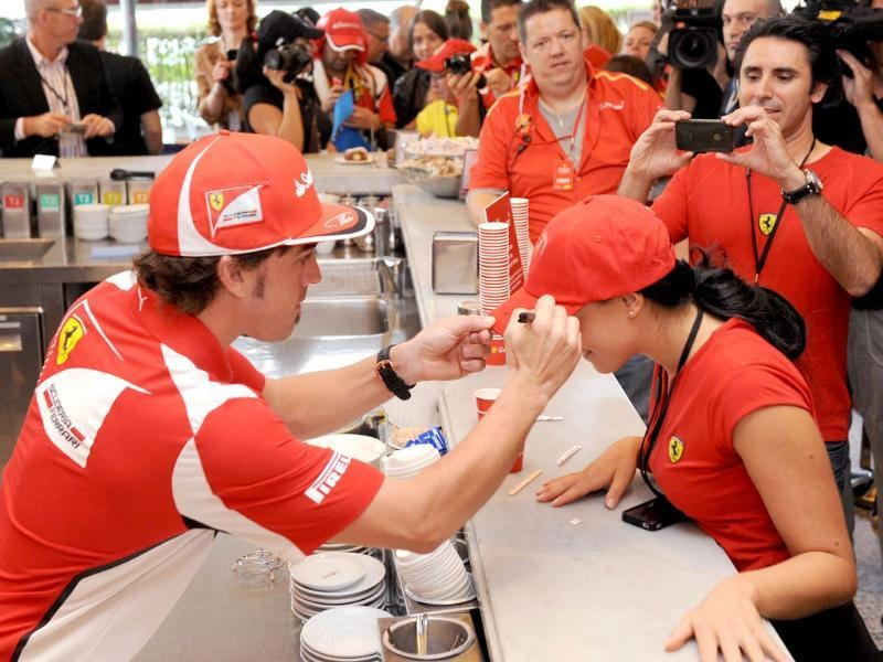 Ferrari driver Fernando Alonso (L) of Spain signs an autograph during a media event ahead of Formula One's Australian Grand Prix in Melbourne. AFP Photo/William West