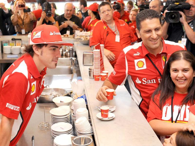 Ferrari driver Fernando Alonso of Spain (R) serves coffee during a media event ahead of Formula One's Australian Grand Prix in Melbourne. AFP Photo/William West