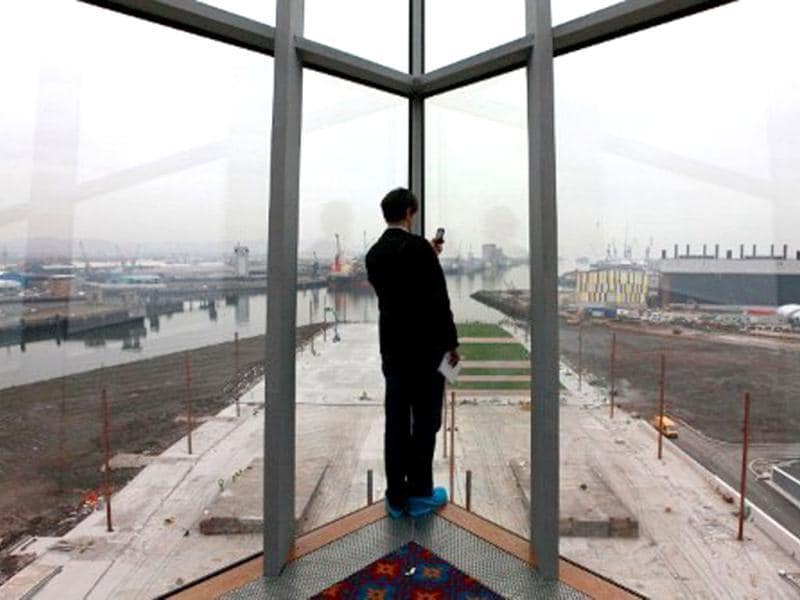 A journalist takes pictures of the Titanic Quarter from inside the Titanic Belfast visitor centre in Northern Ireland. The world's biggest Titanic visitor attraction is to open in its Belfast birthplace on 31 March, 100 years to the day since the doomed ocean liner was completed in the same shipyards. AFP/Peter Muhly