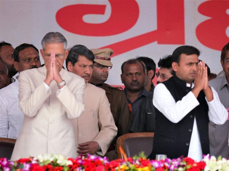 Uttar Pradesh governor B L Joshi and the new chief minister Akhilesh Yadav greeting the gathering after the swearing-in ceremony in Lucknow. PTI Photo by Nand Kumar