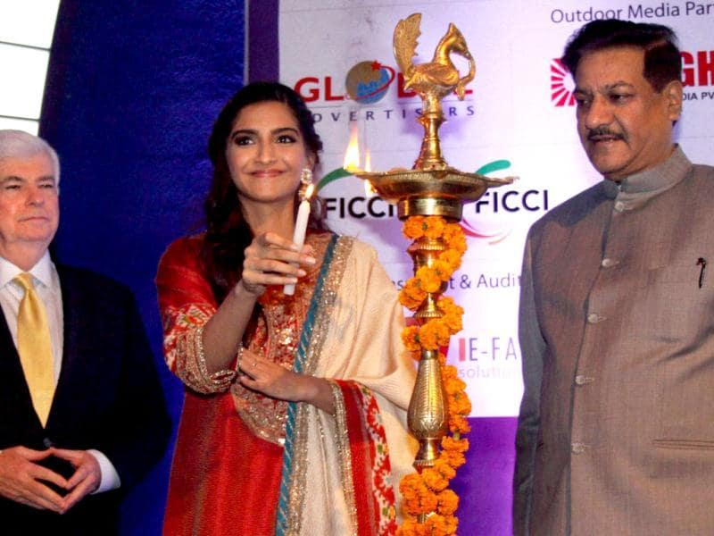 Sonam Kapoor lights the lamp with Maharashtra CM Prithviraj Chavan and Christopher Dodd, Chairman and CEO of Motion Picture Association of America.