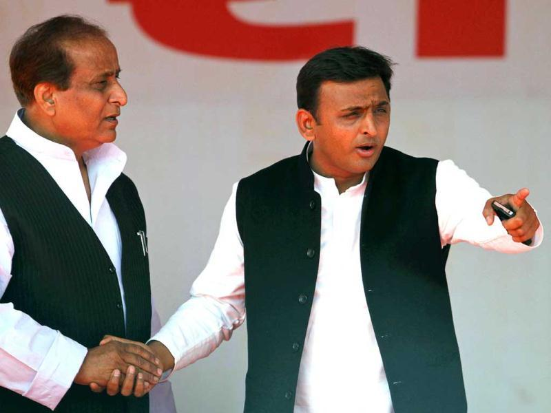 Samajwadi Party leader Akhilesh Yadav holds the hand of senior party leader Azam Khan while gesturing after his oath taking ceremony as the chief minister of Uttar Pradesh state in Lucknow. AP Photo/Rajesh Kumar Singh