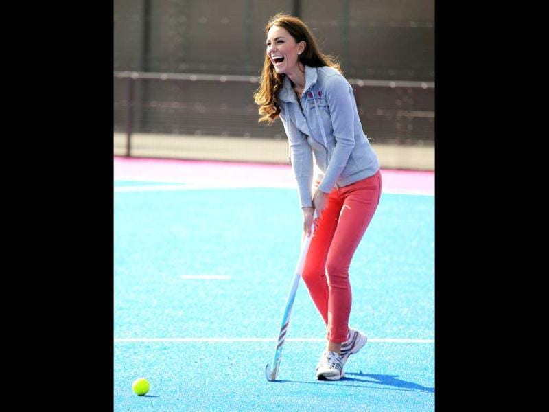 Britain's Duchess of Cambridge laughs as she plays hockey with the British Olympic hockey teams at the Riverside Arena in the Olympic Park, London. The Duchess of Cambridge viewed the Olympic Park and met members of the men's and women's British hockey teams. AP Photo/Chris Jackson, Pool