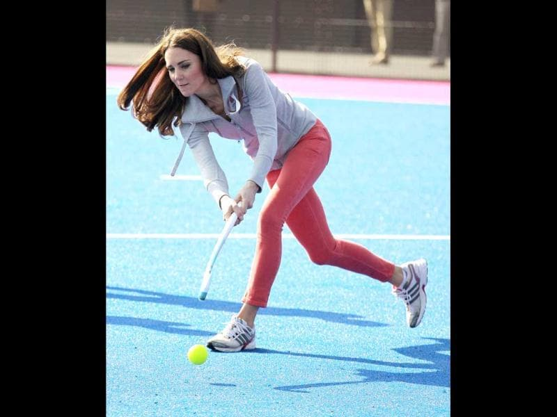 Britain's Catherine, Duchess of Cambridge, hits a shot as she plays hockey with British hockey team members at the Riverside Arena during a visit to the Olympic Park in London. AFP Photo