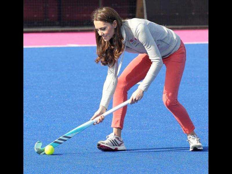 Britain's Catherine, Duchess of Cambridge, controls the ball as she plays hockey with British hockey team members at the Riverside Arena during a visit to the Olympic Park in London. AFP Photo