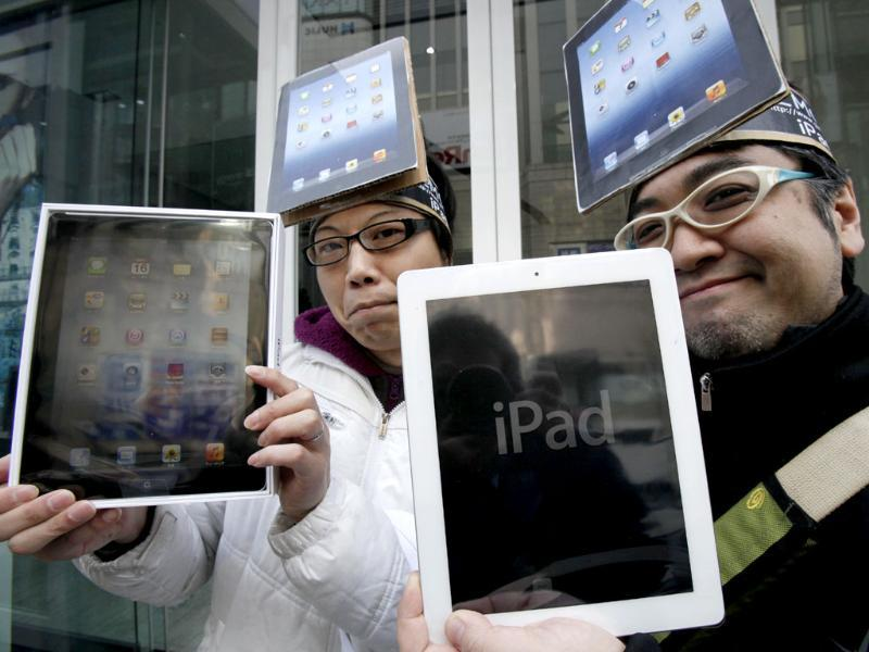 Japanese Ryota Musha (R) and Hisanori Kogure show off the new iPad tablet computers they purchased in Tokyo. AP Photo/Koji Sasahara