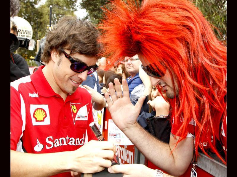 Ferrari Formula One driver Fernando Alonso of Spain signs autographs before the first practice session of the Australian F1 Grand Prix at the Albert Park circuit in Melbourne. Reuters/Brandon Malone