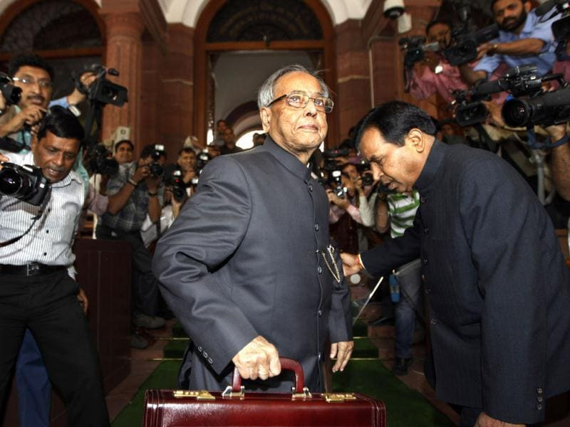 Indian finance minister Pranab Mukherjee, center, holds a briefcase containing the annual budget documents as he arrives at the Indian Parliament in New Delhi. Mukherjee presented India's new budget today amid concerns about inflation, the country's falling growth rate and its large deficit. (AP Photo/Saurabh Das)