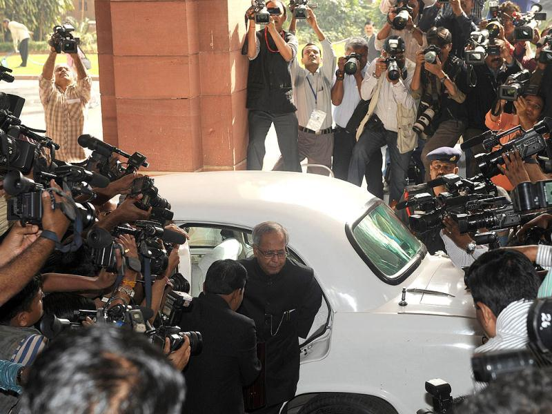 Finance minister Pranab Mukherjee arrives at parliament surrounded by the media prior to presenting the national budget in New Delhi. Government was due to deliver its budget as an acrimonious split in its ranks over hiking rail fares highlighted the increasingly dysfunctional nature of the ruling coalition. The Congress-led administration, already battered by a string of graft scandals, is under financial market pressure to cut public spending and rein in a ballooning deficit at the same time as spurring slowing growth. AFP PHOTO/ Raveendran