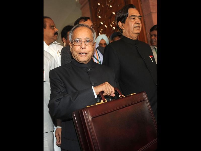 Finance minister Pranab Mukherjee poses for the media in parliament prior to presenting the national budget in New Delhi. Government was due to deliver its budget as an acrimonious split in its ranks over hiking rail fares highlighted the increasingly dysfunctional nature of the ruling coalition. The Congress-led administration, already battered by a string of graft scandals, is under financial market pressure to cut public spending and rein in a ballooning deficit at the same time as spurring slowing growth. AFP PHOTO/ Raveendran