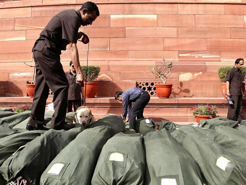 A sniffer dog is used to secure sacks of financial papers related to the budget at the Indian Parliament hours before the Indian budget is presented, in New Delhi. Finance Minister Pranab Mukherjee presented India's new budget today amid concerns about inflation, the country's falling growth rate and its large deficit. (AP Photo/Saurabh Das)