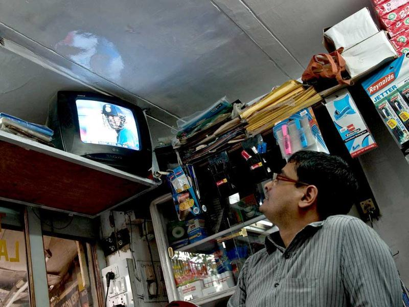A man watches his television set as Sachin Tendulkar scores his 100th hundred in an ODI against Bangladesh on Friday